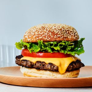 Grilled hamburger with melted American cheese, lettuce, tomatoes, onions, and mayonnaise